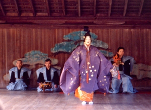 This is an image of a Noh actor; behind him is a group of stage musicians.