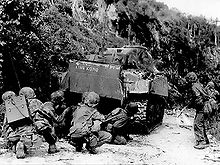 American troops advancing behind a Sherman battle tank during the Battle of Saipan in Summer, 1944. The loss of Saipan made it clear that Japan had lost the war, but fighting would continue for over one year afterwards.