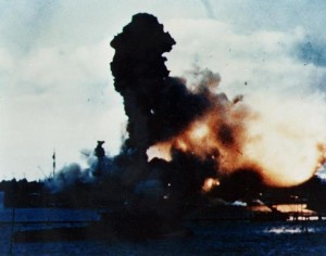 The USS Arizona on fire in Pearl Harbor.