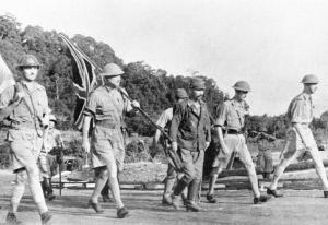 British General Sir Arthur Percival, surrounded by Japanese troops and under a flag of truce, going to negotiate the surrender of Singapore to Japan. The Battle of Singapore was the largest defeat of British land forces in history.