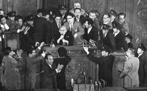 The Speaker of the Lower House of the Diet performing the final tally of votes regarding the security treaty. He had to be physically escorted to the stage and protected from left-wing Diet members, who attempted to prevent him from finishing the procedures required to pass the treaty.
