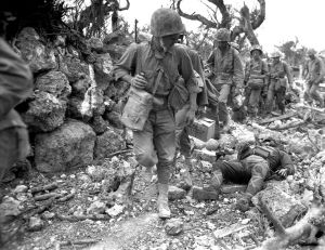 A US Marine patrol passes a dead Japanese soldier during the battle.