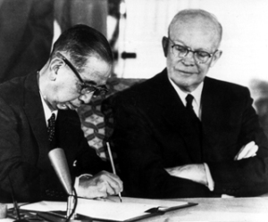 Dwight Eisenhower looks on as Kishi Nobusuke signs the revised security treaty in the White House. Courtesy of the Embassy of the United States in Japan.