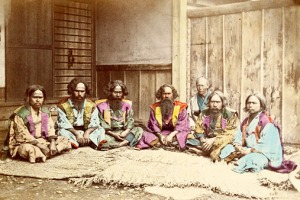 A colorized photo of an Ainu group in the late 1800s.