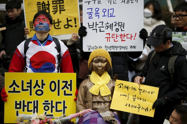 "People hold placards next to a statue symbolizing ""comfort women"" during a weekly anti-Japan rally in front of Japanese embassy in Seoul"