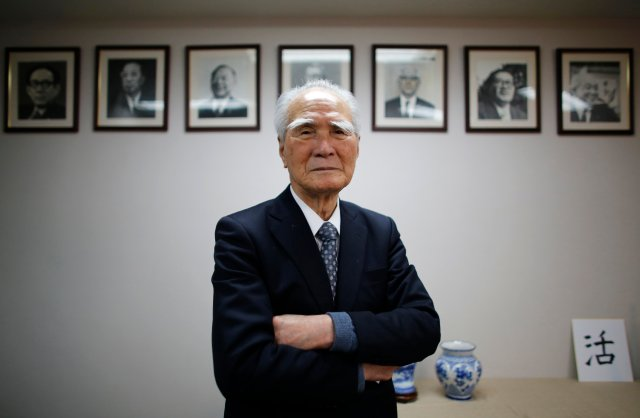Former Japanese PM Murayama poses in front of portraits of former leaders of his Social Democratic Party after an interview with Reuters at the party headquarters in Tokyo
