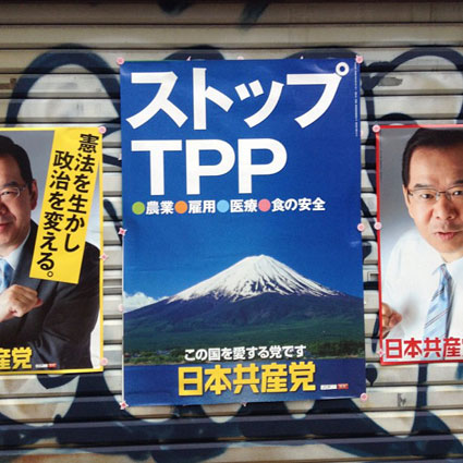 "A Japan Communist Party poster from last year. The center poster says ""Stop TPP. The Party that Loves this Country: The Japan Communist Party."" The one on the left says, ""Rely on the constitution, change the government."""