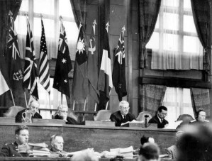 The court in session with the justices seated on the raised platform. The flags behind them give a sense (fair or unfair) of who the trial is for.